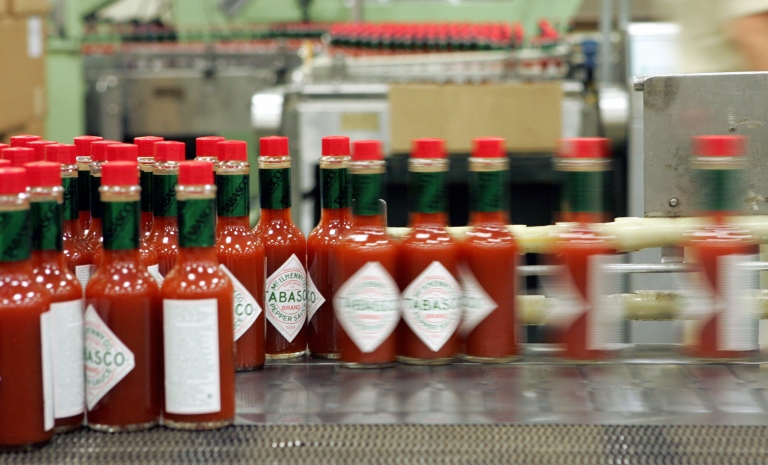 <p>A line of bottles of McIlhenny Tabasco Sauce are shown at the McIlhenny Company inside the plant at Avery Island, Louisiana 14 September 2005. The sauce was created by Edmund McIlhenny in 1868 and the same process is still in use today.</p>