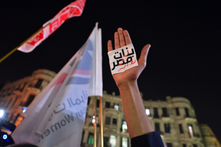 <p>An Egyptian protester hold up his hand with a slogan reading in Arabic: