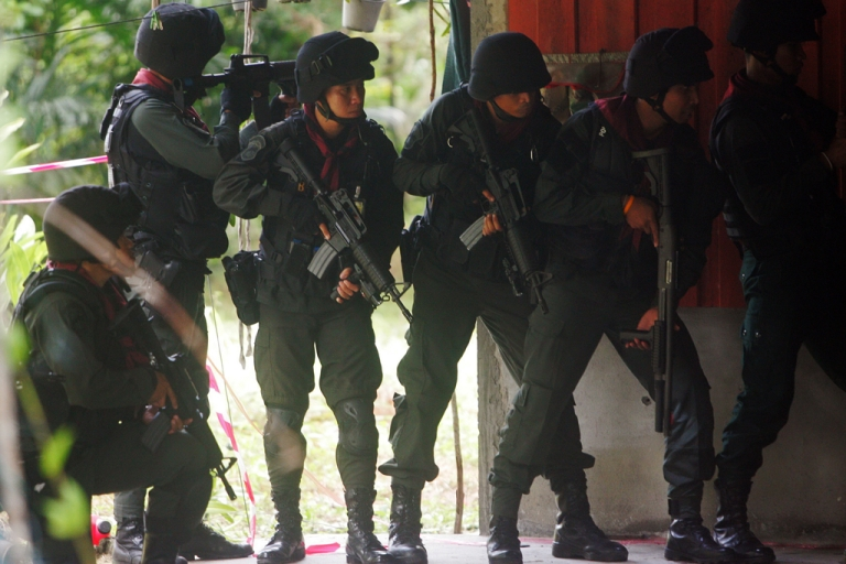 <p>Thai police stand guard during a suspected insurgents attack at a military base in Thailand's restive southern province of Narathiwat on February, 13, 2013.  The Thai government agreed on February 28, 2013 to peace talks with Muslim rebels operating in the south.</p>