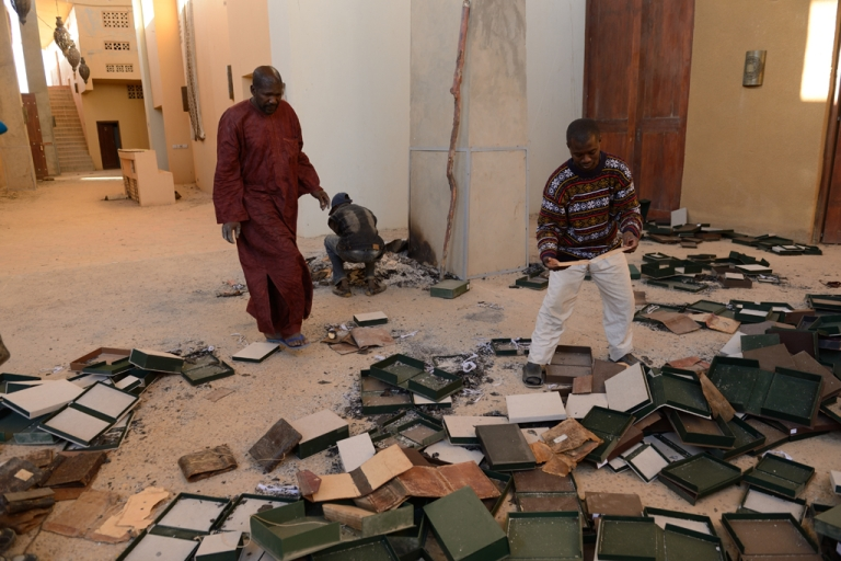 <p>Men recover burnt manuscripts at the Ahmed Baba Center for Documentation and Research in Timbuktu, Mali, on Jan. 29, 2013. As French-led forces recaptured Mali's desert city of Timbuktu, fleeing Islamists set fire to a building that housed priceless ancient manuscripts.</p>
