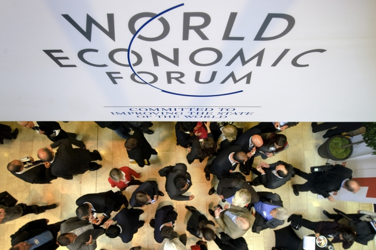 <p>Participants at the World Economic Forum (WEF) chat under a sign on Jan. 25, 2012, at the Congress Center in the Swiss municipality of Davos. The world's political and business elites met with some 40 heads of government for five days to discuss all things related to the global economy.</p>