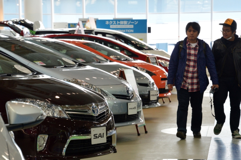 <p>People look at Toyota Motor vehicles at the company's showroom in Tokyo, Japan, on Feb. 5, 2013. Toyota recently raised its annual net profit forecast by more than 10 percent on strong sales of the Camry sedan and other vehicles in the US.</p>