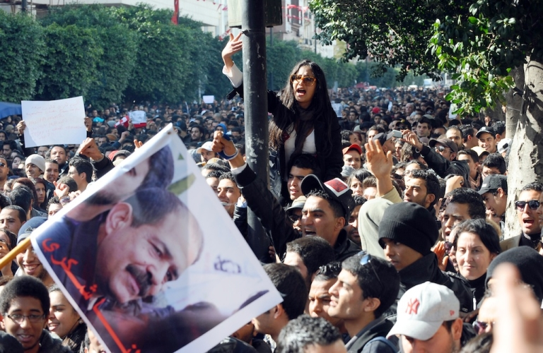 <p>Protesters shout slogans outside the Interior Ministry to protest the death of Chokri Belaid (featured on the poster), who was shot dead on Feb. 6, 2013 in Tunis.</p>