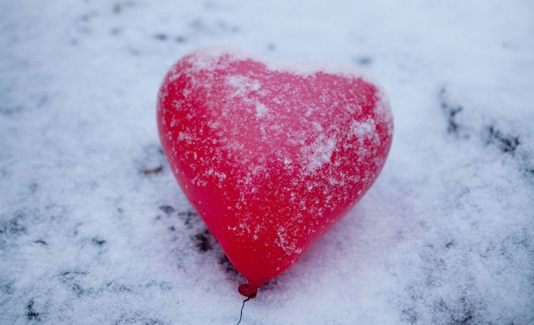 <p>A red heart-shaped balloon lays in the snow.</p>