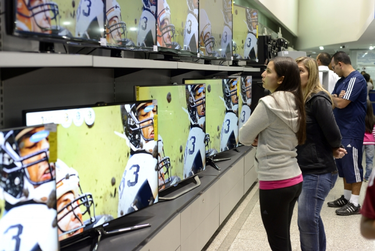 <p>Venezuelan shoppers are eying televisions that could become pricier after the government's devaluation of the national currency, the bolivar fuerte, against the US dollar takes effect.</p>
