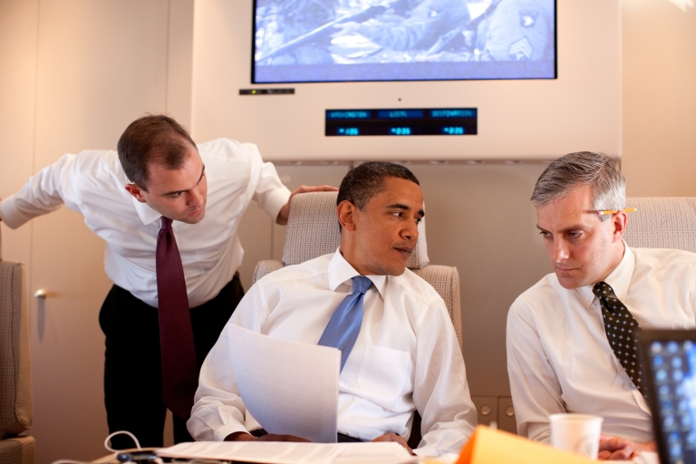 <p>Denis McDonough (R, with pencil behind ear) conferring with President Barack Obama and speechwriter Ben Rhodes on Air Force One en route to Cairo, Egypt, on June 4, 2009.</p>
