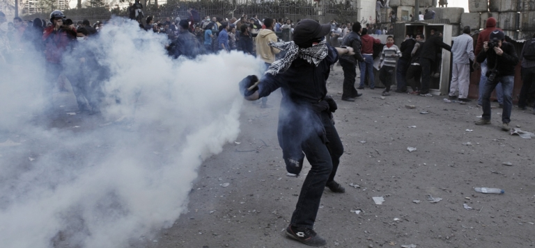 <p>An Egyptian protester throws a live tear gas canister back toward riot police in Tahrir Square on Jan. 25, in Cairo, Egypt.</p>