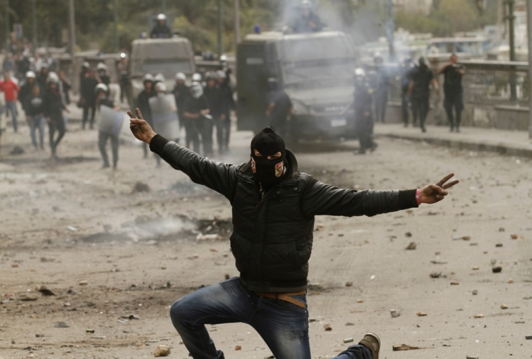 <p>An Egyptian protester flashes the sign for victory during clashes with riot police near Cairo's Tahrir Square on Jan. 28, 2013.</p>
