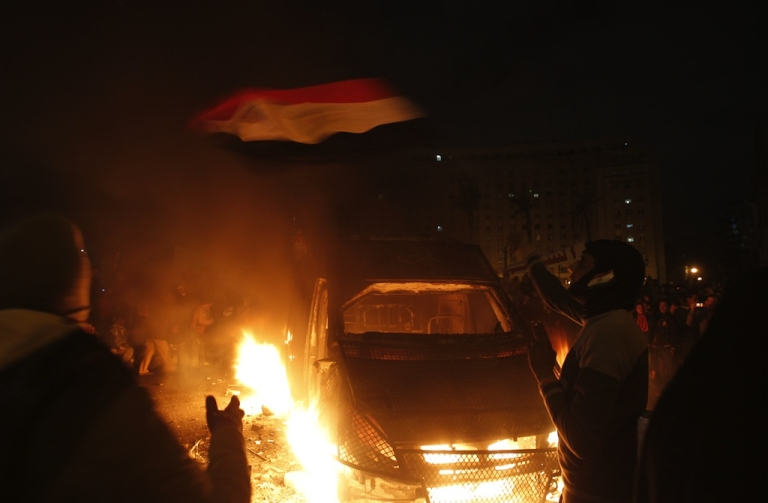 <p>An protester waves the Egyptian flag near a police vehicle on fire in Cairo's Tahrir Square on Jan. 28, 2013.</p>