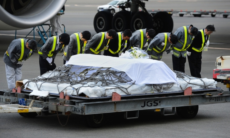 <p>Ground staff members bow after a coffin carrying the last Japanese victim of the Algerian hostage crisis was unloaded from a plane at Narita Airport, outside Tokyo on January 26, 2013. The body of the last of 10 Japanese killed in the Algerian hostage crisis arrived in Japan by commercial flight, a day after the bodies of the nine others returned home with seven Japanese survivors.</p>