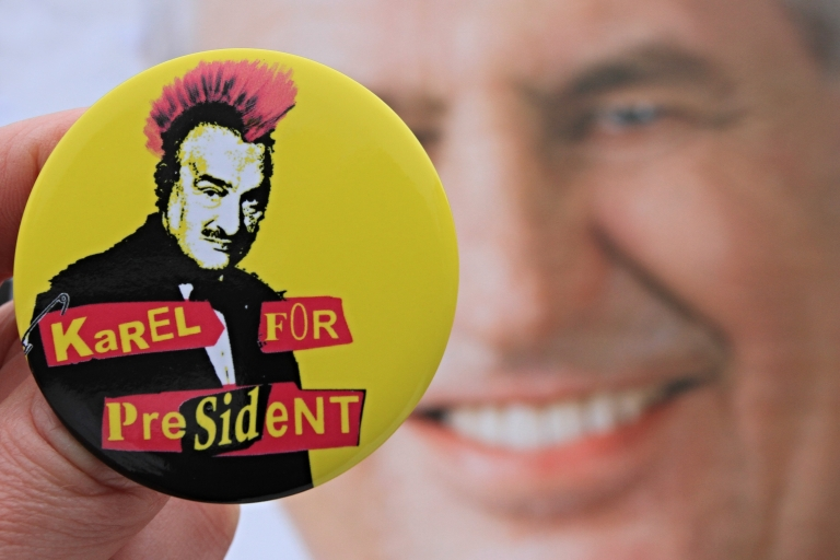 <p>A button depicting Czech presidential candidate Karel Schwarzenberg as a punk with red hair in front of a campaign poster of rival Milos Zeman.</p>