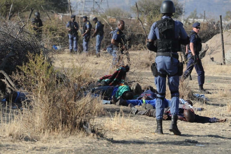 <p>Police surround miners killed during clashes between protesting miners and police near a platinum mine in Marikana on August 16, 2012. A new video shows that police did not act in self-defense, as they claimed, and in fact murdered striking miners.</p>