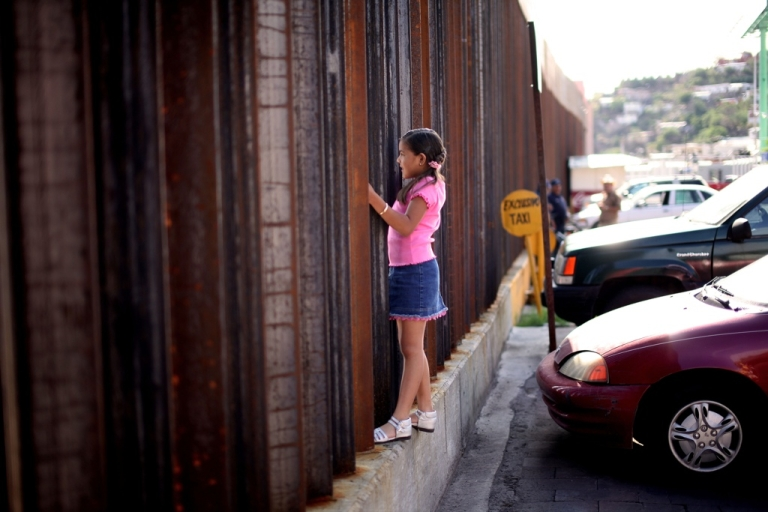<p>A girl in Nogales, Mexico speaks to relatives through the US-Mexico border fence.</p>
