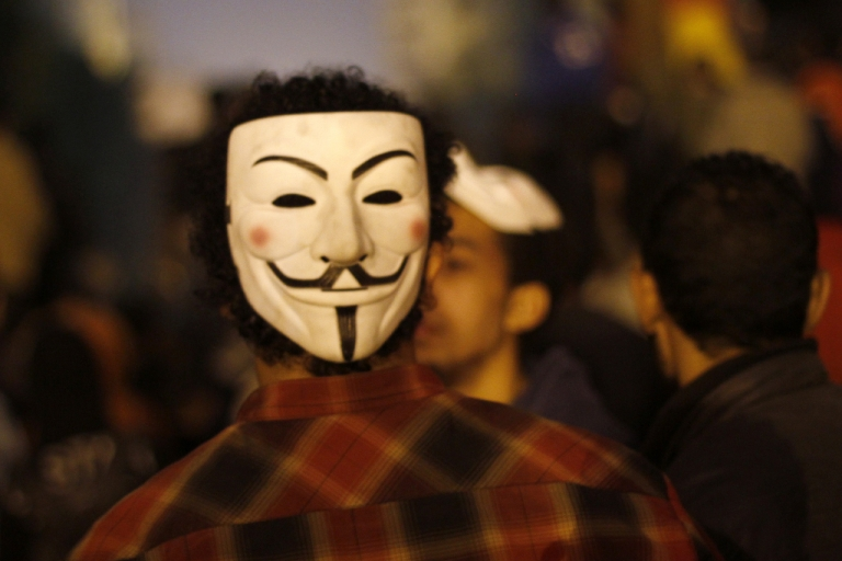 <p>An Egyptian protester wears a mask of the Anonymous movement during a protest in Tahrir Square to call for the fall of Islamist President on Jan. 24, 2012 in Cairo.</p>
