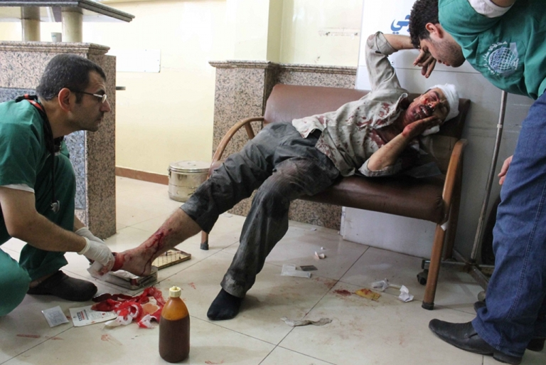 <p>A wounded Syrian man receives medical treatment at a hospital in the northern Syrian city of Aleppo on Sep. 20, 2012. Doctors in the region risk imprisonment, torture, and death at the hands of Assad's forces if they continue to treat injured civilians and rebels.</p>