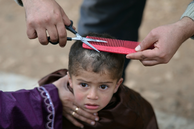<p>A displaced Syrian boy gets a haircut at a makeshift refugee camp in Atmeh, in the northwestern province of Idlib along the Turkish border, Jan. 31 2012.</p>