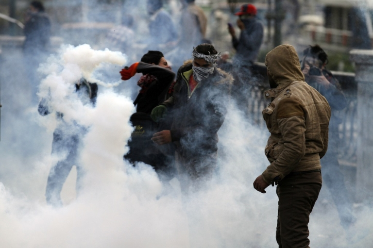 <p>An Egyptian protester returns a tear gas canister fired by riot police during clashes near Cairo's Tahrir Square on Jan. 29, 2013.</p>