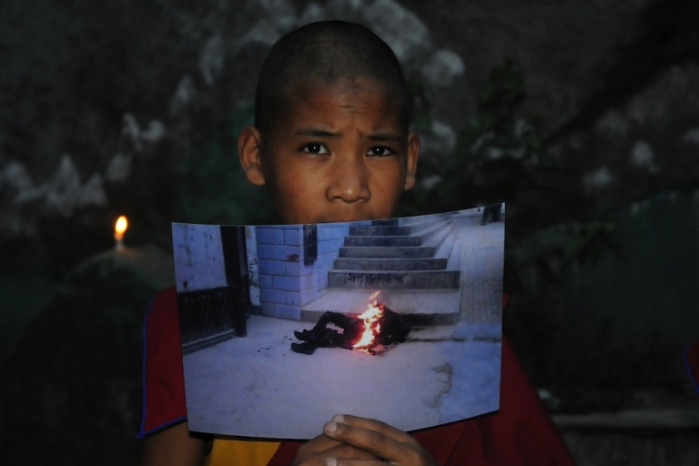 <p>An exiled Tibetan monk holds a picture of 50-year-old, Tamdin Thar, who burned himself to death to protest against the Chinese rule in Tibet during a rally on June 15, 2012. Chinese authorities have gotten increasingly strict with Tibetans, as self-immolations continue.</p>