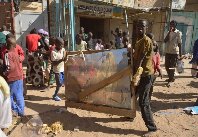 <p>A man an a child carry a mirror as residents plunder stores they say belong to Arabs, Mauritanians and Algerians who they accuse of supporting the Al Qaeda-linked Islamists, on Jan. 29, 2013 in Timbuktu.</p>