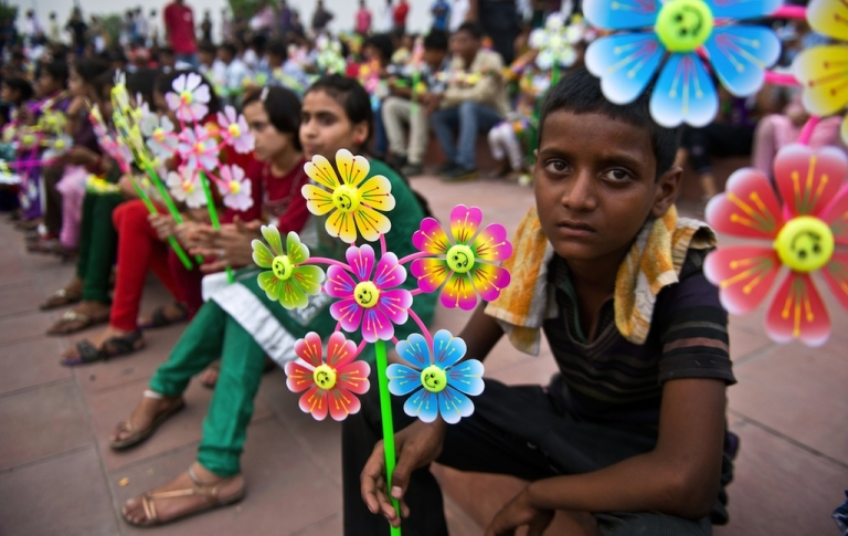 <p>A young Indian boy holds a flower-shaped pinwheel, with each petal representing a child death caused by malnutrition, during a Global Day of Action against Global Hunger event in New Delhi on June 7, 2013. The event was held ahead of the Hunger Summit in London hosted by the UK and Brazilian governments calling for action on global hunger.</p>