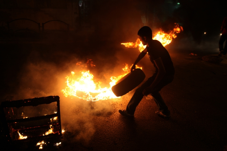 <p>A Palestinian youth burns tires during a protest against the high cost of living at Al-Amari refugee camp near the West Bank city of Ramallah on September 8, 2012.</p>