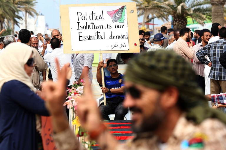 <p>Libyan protesters hold placards and banners during a demonstration in support of the Political Isolation Law in Libya's landmark Martyrs Square' on May 5, 2013 in Tripoli, Libya. Libya's General National Congress, under pressure from armed militias, voted through a controversial law to exclude former regime officials from government posts. Gunmen who had surrounded the foreign and justice ministries lifted the sieges when state television broke the news.</p>