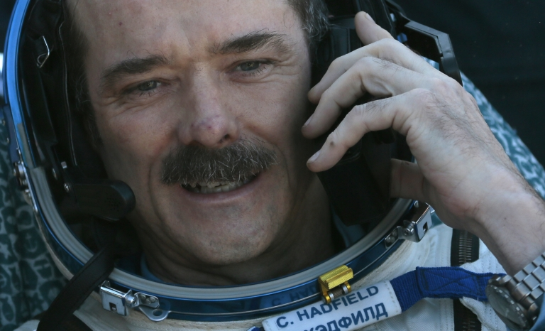 <p>Canadian astronaut Chris Hadfield speaks on the phone shortly after the landing aboard the Russian Soyuz space capsule some 90 miles southeast of the town of Zhezkazgan in central Kazakhstan on May 14, 2013.</p>