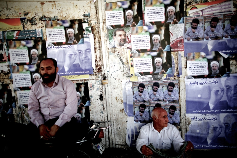 <p>Iranians sit next to electoral posters of Hassan Rowhani (L) and Mohsen Rezai (C) in the religious city of Qom some 130 kilometres south of the capital on June 9, 2013.</p>