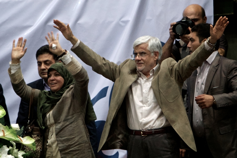 <p>Iranian former Vice-President Mohammad Reza Aref (C) and his wife Hamideh Moravej Tafreshi (L) wave to supporters during a campaign rally for Aref in Tehran on June 10, 2013 before he withdrew from the race.</p>