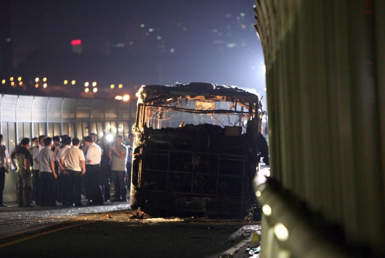 <p>This picture taken on June 7, 2013 shows investigators at the scene of a bus that caught fire on the BRT (Bus Rapid Transit) elevated road in the city of Xiamen, China's southeast Fujian province.  A fire that engulfed a commuter bus in minutes during rush hour in the Chinese city of Xiamen, killing 47 and injuring dozens more, appears to have been deliberately set, state media quoted investigators as saying on June 8.</p>