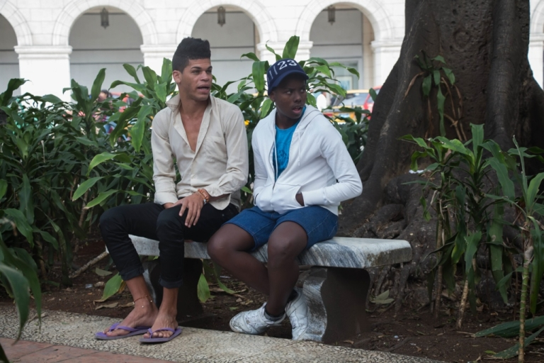 <p>Two Cuban men sit in Havana's Central Park, waiting for customers.</p>