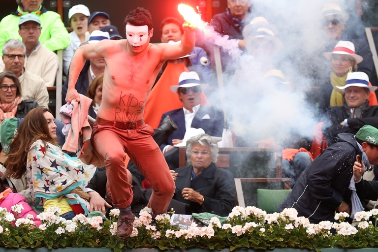 <p>A protester runs onto court with a lit flare before the start of a game in the men's final between Rafael Nadal of Spain and David Ferrer of Spain at the French Open on June 9, 2013 in Paris.</p>