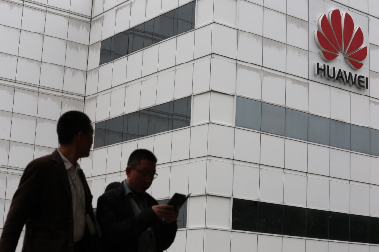 <p>People walk by a building on the Huawei campus in the Chinese city of Shenzhen on April 7, 2013.</p>