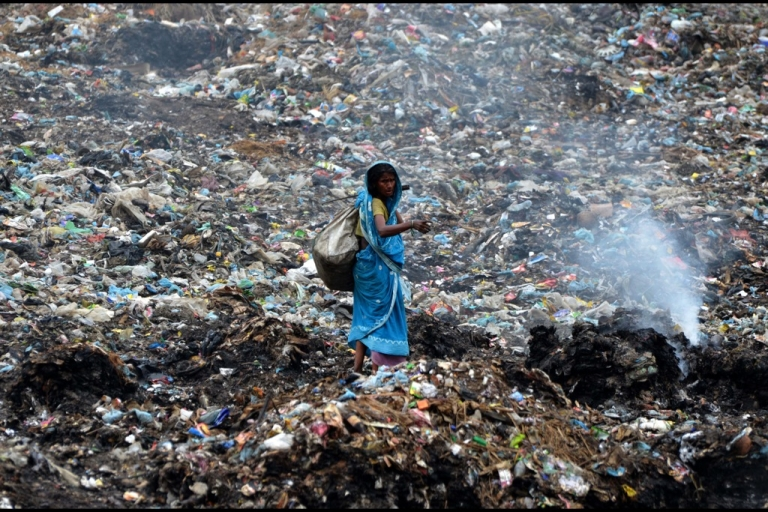 <p>An Indian ragpicker walks among heaps of rubbish at a municipal waste dump in Dimapur on April 22, 2013, on World Earth Day.</p>