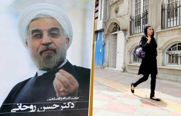 <p>An Iranian woman walks past a campaign poster of Hassan Rowhani, moderate presidential candidate and former top nuclear negotiator, in Tehran on June 11, 2013.</p>