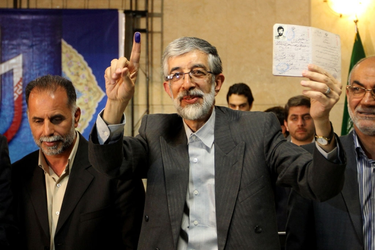 <p>Iranian former parliament speaker Gholam Ali Haddad Adel holds up his ID after registering his candidacy for the upcoming presidential election at the interior ministry in Tehran on  May 10, 2013. He withdrew his candidacy on June 10.</p>