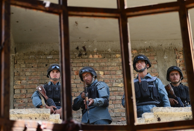 <p>Afghanistan policemen stand guard in a building which was used for attack on Kabul airport on June 10, 2013. All seven militants who launched the died in the assault, Afghan police said.</p>