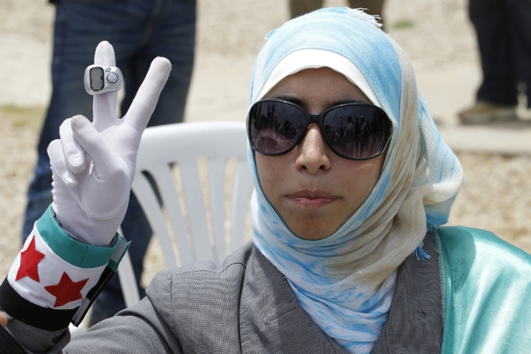<p>A Lebanese woman flashes a peace sign during a protest against Hezbollah on June 9, 2013, in the Lebanese capital, Beirut.</p>