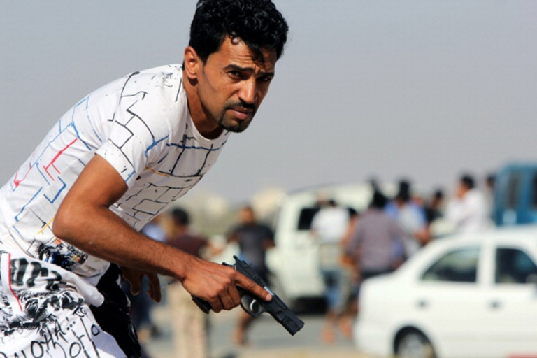 <p>A Libyan protester holds a gun during clashes between demonstrators and troops of the Libyan Shield Forces, a coalition of militias, following a demonstration outside the LSF office in Benghazi on June 8, 2013.</p>