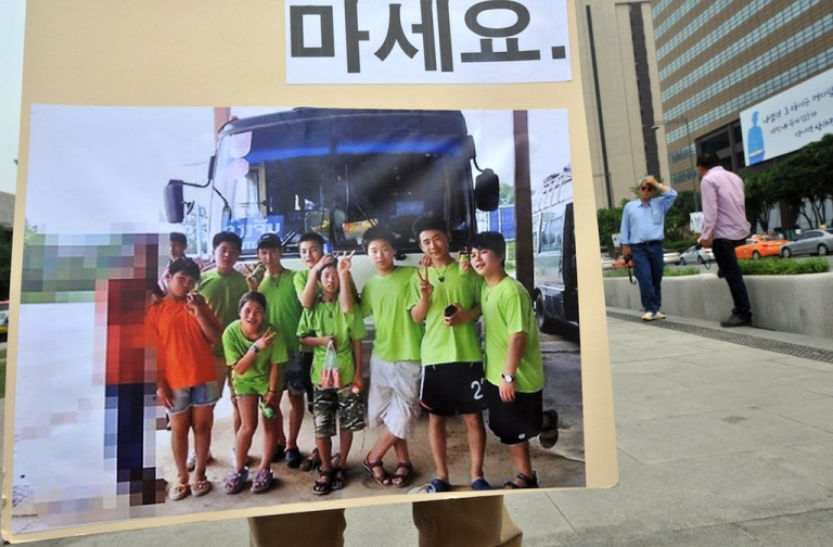 <p>A South Korean activist holds a placard showing the purported picture, which was not officially substantiated, of nine North Korean young defectors reading 'Do not forget these children', during a solo street protest in Seoul on June 3, 2013.</p>