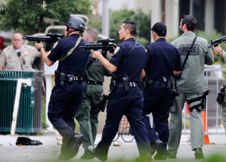 <p>Los Angeles Police Department officers along with Los Angeles County Sheriff deputies search the grounds of Santa Monica College near the library after multiple shootings were reported near the campus in Santa Monica, Calif., on June 7, 2013.</p>