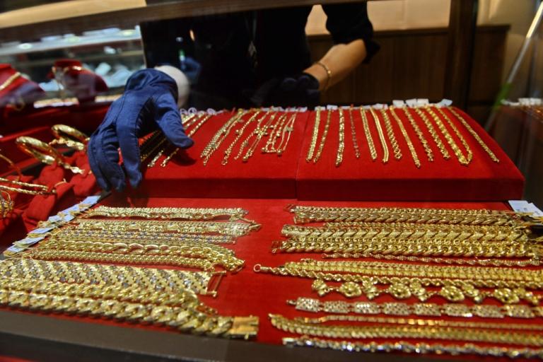 <p>A salesperson arranges gold necklaces at a shop in Singapore on April 18, 2013.</p>