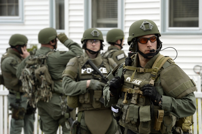<p>A US police SWAT team searches houses after the Boston Marathon bombings in April.</p>