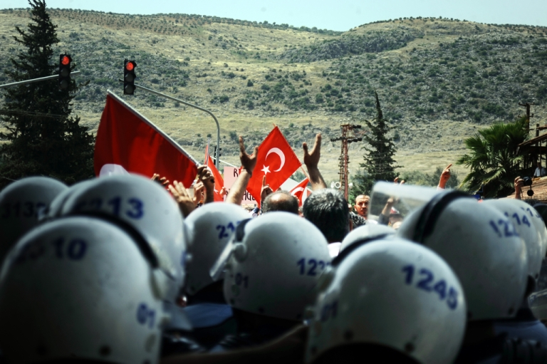 <p>People of Reyhanli chant slogans as riot police block them on May 18, 2013, at Reyhanli in Hatay, during the funerals of the victims of a car bomb which went off on May 11 at Reyhanli in Hatay just a few kilometres from the main border crossing into Syria. The attacks also provoked a backlash against Syrian refugees in Turkey, whose number is around 400,000.</p>
