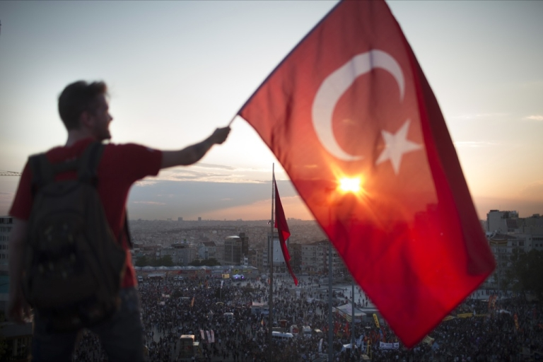 <p>A protestor waves the Turkish flag from a roof top at Taksim square on June 3, 2013 in Istanbul, Turkey. The protests began initially over the fate of Taksim Gezi Park, one of the last significant green spaces in the center of the city.</p>