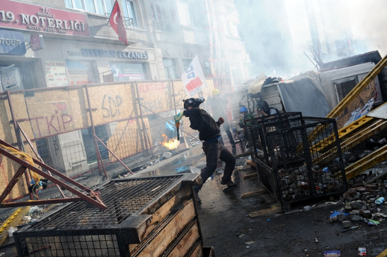 <p>A demonstrator wearing a gas mask throws an object in Taksim square on June 11, 2013. Riot police re-entered Istanbul's protest square today, firing tear gas and rubber bullets at firework-hurling demonstrators in a fresh escalation of unrest after Turkish Prime Minister Recep Tayyip Erdogan said he would meet with protest leaders.</p>