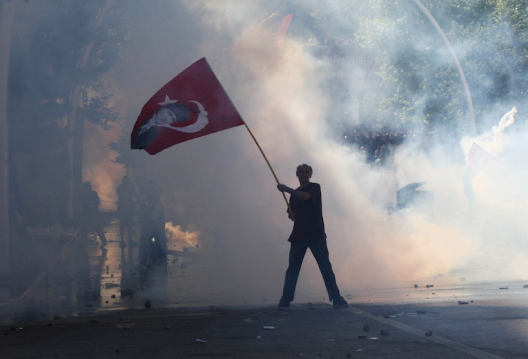 <p>Tear gas surrounds a protestor holding a Turkish flag with a portrait of the founder of modern Turkey Mustafa Kemal Ataturk as he takes part in a demonstration in support of protests in Istanbul and against the Turkish Prime Minister and his ruling Justice and Development Party (AKP), in Ankara, on June 1, 2013.</p>