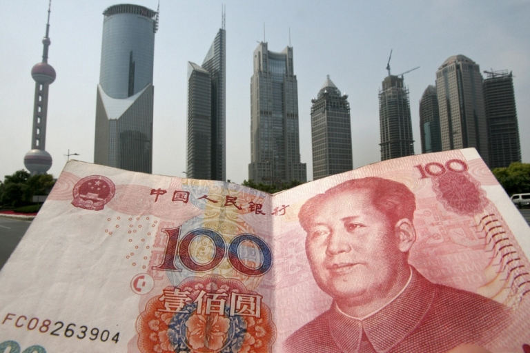 <p>Shanghai, CHINA: A Chinese 100 renminbi (yuan) note is held up in front of the Pudong financial district skyline in Shanghai, 21 May 2007.</p>