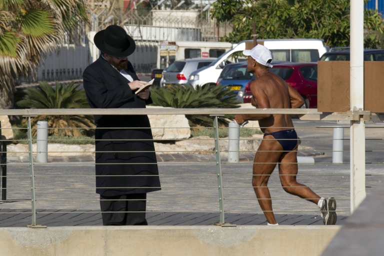 <p>A man jogs past an Ultra-Orthodox Jewish men praying on the banks of the Yarkon River in Tel Aviv.</p>