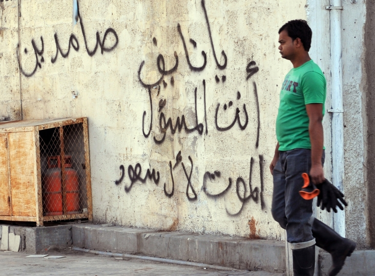 <p>A foreign worker walks past graffiti against the ruling Saudi royal family in the mostly Shia Qatif region of Eastern Province on November 25, 2011. Four people have been killed and nine others wounded in an exchange of gunfire between security forces and what the Saudi interior ministry called criminals serving a foreign power in the country's oil-producing Eastern Province.</p>